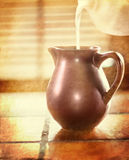 Het gieten van de melk in een bruine kruik Stock Afbeeldingen