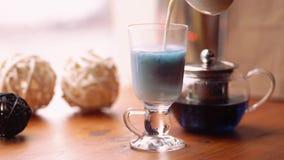 Het gieten van de melk in de kop van de Blauwe thee van de Vlindererwt van bloemen Clitoria Blauwe Thaise thee en melk die langza