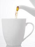 Het gieten van de thee in een kop Stock Afbeeldingen