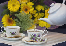 Het gieten van de thee in koppen Stock Afbeeldingen