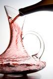 Het gieten van de wijn in karaf stock afbeeldingen