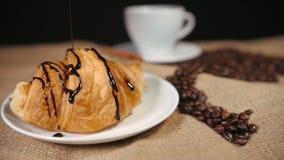 Het gieten van een Chocolade op Croissant stock videobeelden