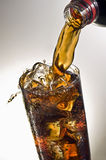 Het gieten van een glas Coca-cola met ijsblokjes Royalty-vrije Stock Afbeeldingen
