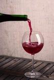 Het gieten van een glas rode wijn Royalty-vrije Stock Foto's