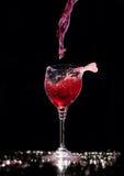 Het gieten van een glas rode wijn bij de zwarte achtergrond Royalty-vrije Stock Foto's