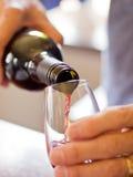 Het gieten van een glas wijn Stock Foto