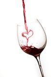 Het gieten van een hart van rode wijn in een glas Royalty-vrije Stock Foto's
