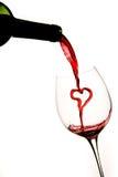 Het gieten van een hart van rode wijn in een glas Stock Foto