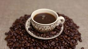 Het gieten van een kop van koffie met koffiebonen stock videobeelden
