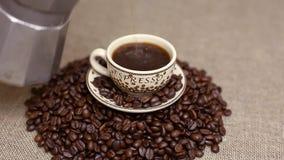 Het gieten van een kop van koffie met koffiebonen stock footage