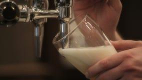 Het gieten van een pint van bier stock footage