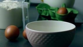 Het gieten van het ei in een kom stock video