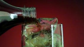 Het gieten van frisdrank in glas met ijsplons op rode achtergrond Kola of verfrissing stock footage