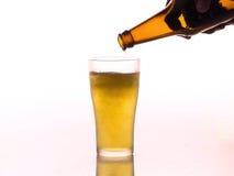 Het gieten van het bier in mok Stock Afbeelding