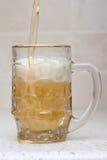 Het gieten van het bier van fles in glas Royalty-vrije Stock Afbeeldingen