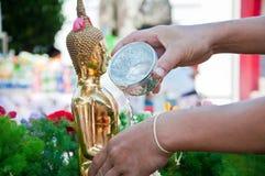 Het gieten van het water aan het standbeeld van Boedha Royalty-vrije Stock Foto's