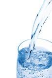 Het gieten van het water in een glas. Stock Afbeelding