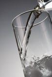 Het gieten van het water in glas stock afbeelding