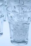 Het gieten van het water in glas Stock Foto
