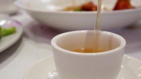 Het gieten van hete thee binnen Chinees restaurant stock video