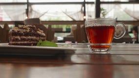 Het gieten van hete thee van glastheepot in transparante mok Theekop en chocoladepastei op houten lijst in de zomerkoffie stock videobeelden
