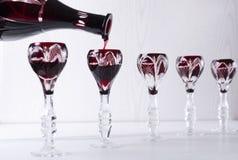 Het gieten van rode bittere alcoholische drank in uitstekende glazen Concept buffetdiner royalty-vrije stock afbeeldingen