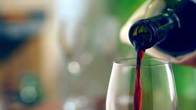 Het gieten van rode wijn in glas Royalty-vrije Stock Afbeeldingen