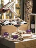 Het gieten van rode wijn in het glas tegen houten achtergrond Royalty-vrije Stock Afbeeldingen