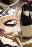 Het gieten van rode wijn in het glas tegen houten achtergrond Royalty-vrije Stock Fotografie