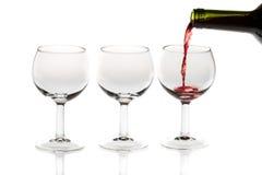 Het gieten van rode wijn in glas van fles Stock Fotografie