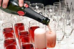 Het gieten van rode wijn in kop stock fotografie
