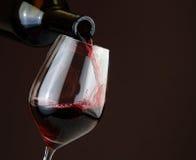 Het gieten van rode wijn op donkere achtergrond Stock Fotografie