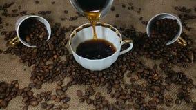 Het gieten van verse gebrouwen koffie in de koffiekop stock videobeelden