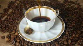Het gieten van verse gebrouwen koffie in de koffiekop in langzame motie stock video