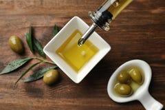 Het gieten van verse olijfolie in kom op lijst, stock afbeeldingen