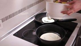 Het gieten van vloeibaar deeg op een hete pan terwijl het braden van pannekoeken stock video