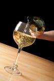 Het gieten van witte wijn in een wijnglas Stock Afbeeldingen