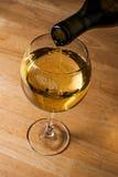 Het gieten van witte wijn in een wijnglas Stock Foto's