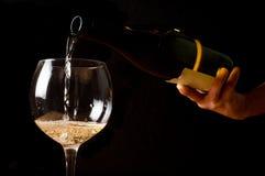 Het gieten van witte wijn in een wijnglas Stock Foto