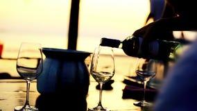 Het gieten van witte wijn in glas bij verbazende zonsondergang met overzeese mening in een strandrestaurant 1920x1080 stock videobeelden