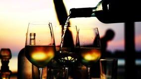 Het gieten van witte wijn in glas in langzame motie bij verbazende zonsondergang met overzeese mening in een strandrestaurant Slu stock video
