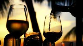 Het gieten van witte wijn in glas in langzame motie bij verbazende zonsondergang met overzeese mening in een strandrestaurant 192 stock video