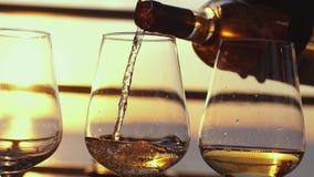 Het gieten van witte wijn in glazen door het overzees op het restaurantterras over zonsondergang Het vieren in langzame motie 384 stock footage
