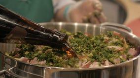 Het gietende bier van de chef-kokkok in pot met fijn - gehakte varkensvleessteel terwijl het koken royalty-vrije stock foto's
