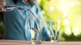 Het gietende drinkwater van de vrouwen` s hand van fles in glas stock foto