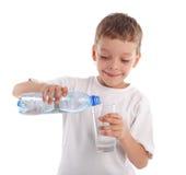Het gietende water van het kind in een glas Stock Foto