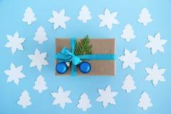 Het giftvakje van ambachtdocument, blauw lint en verfraaide spar wordt verpakt vertakt zich en blauwe Kerstmisballen op de blauwe Royalty-vrije Stock Afbeeldingen
