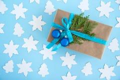 Het giftvakje van ambachtdocument, blauw lint en verfraaide spar wordt verpakt vertakt zich en blauwe Kerstmisballen op de blauwe Stock Afbeeldingen