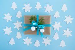 Het giftvakje van ambachtdocument, blauw lint en verfraaide spar wordt verpakt vertakt zich en zilveren Kerstmisballen op de blau Royalty-vrije Stock Foto