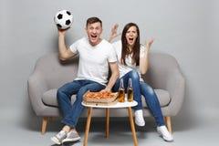 Het gillen de man van de paarvrouw de voetbalfans juichen steun omhoog favoriet team met voetbalbal toe, expressieve het gesticul stock fotografie